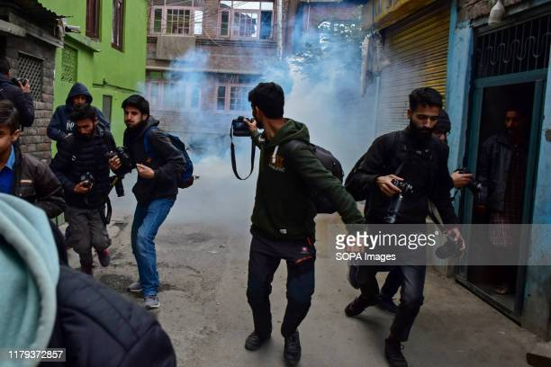 SRINAGAR JAMMU KASHMIR INDIA Photojournalists run for cover as tear gas canister fired by the government forces explode near the shrine in Srinagar...