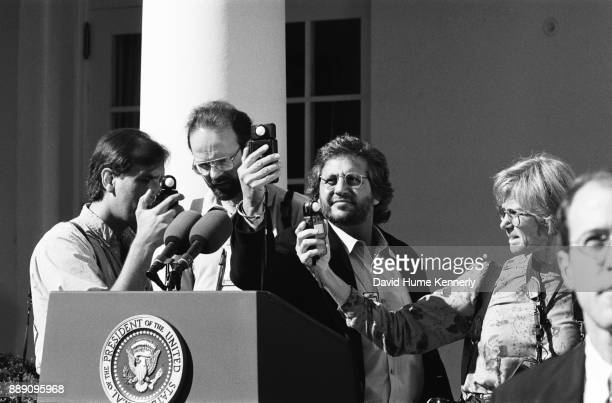Photojournalists take light readings at a podium on the grounds of the White House before a news conference with Vice President Al Gore and President...