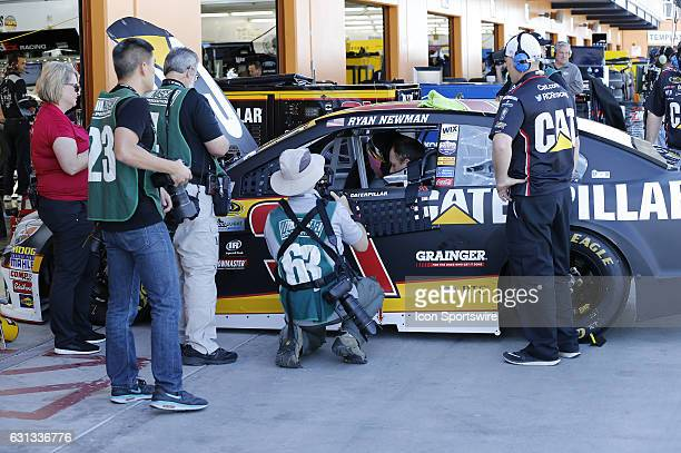 Photojournalists take pictures of Ryan Newman in his car during practice for the Kobalt 400 NASCAR Sprint Cup series race on March 4 at Las Vegas...