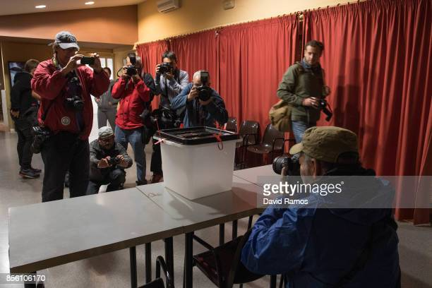 Photojournanlists take pictures of a ballot box at a polling station before the opening as the Catalan Government holds a referendum vote on October...