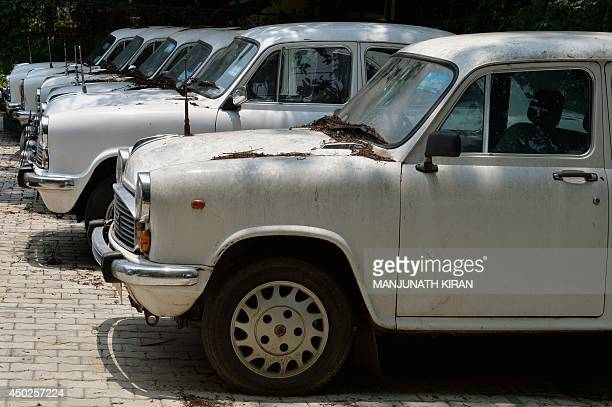 Defunct Ambassador cars of the state government gather dust at a parking lot in Bangalore on June 2 2014 The maker of India's Ambassador car has...