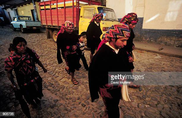 Men who are cofradias members of a brotherhood of the religious and social leaders of the Maya community walk toward the town center in...