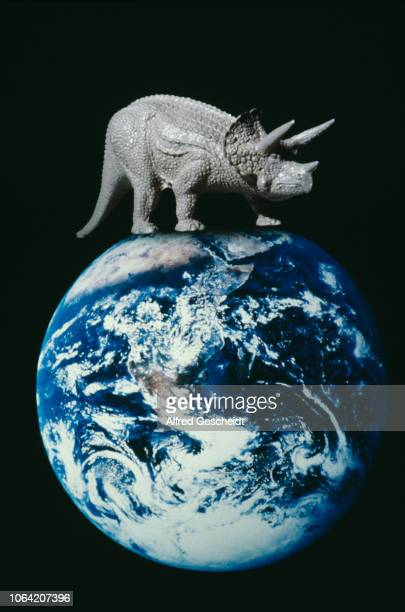 A photomontage of a triceratops bestriding the planet Earth US 1985