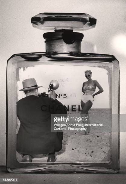 Photomontage of American photographer Weegee taking a photograph of a woman in a bathing suit inside a Chanel No. 5 cologne bottle, late 1950s.