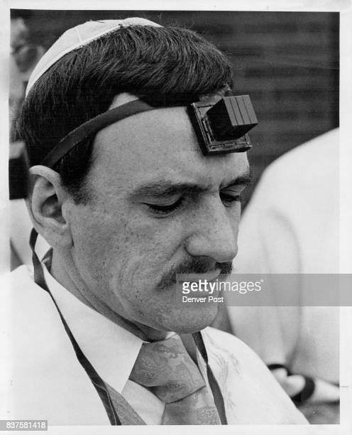 Photos above and to right show Jewish men wearing phylacteries during morning prayers Above is Izzy Glass ad to the right is arm of Joe Streltzer...