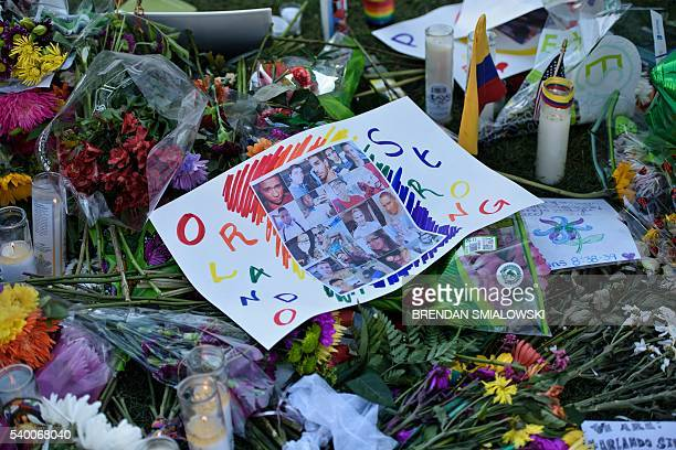 Photos and flowers are seen at a memorial at the Dr Phillips Center for the Performing Arts to honor the Pulse nightclub mass shooting victims June...
