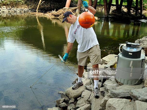 Photos by Gordon Chibroski/Staff Photographer Tim Bridges a scientist for the Environmental Protection Agency sets up an automatic water sampling and...