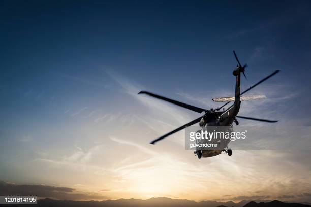 photos military helicopter flying against sunset - helicopter photos stock pictures, royalty-free photos & images