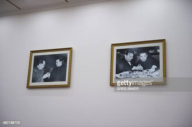 Photos of late North Korean leader Kim IlSung meeting with late Chinese leaders Mao Zedong and Zhou Enlai hang on a wall at the North Korean embassy...