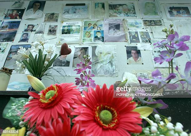 Photos of missing persons are posted on a board at the memorial wall near the Maikao mortuary in Phuket province southern Thailand 24 June 2005...
