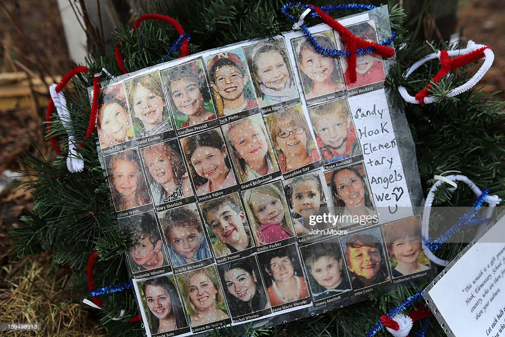 Photos of Sandy Hook Elementary School massacre victims sits at a small memorial near the school on January 14, 2013 in Newtown, Connecticut. The town marked a month anniversay since the massacre of 26 children and adults at the school, the second-worst such shooting in U.S. history.