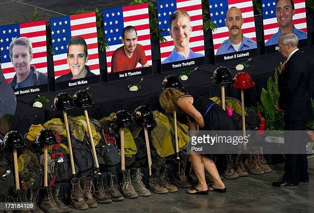Photos of some of the 19 fallen firefighters line the front of the stage before a memorial service at Tim's Toyota Center July 9 2013 in Prescott...