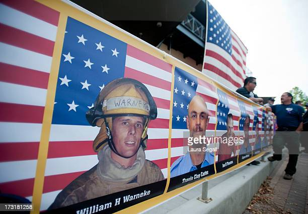 Photos of the 19 firefighters killed in a wildfire line the entrance to a memorial service in their honor at Tim's Toyota Center July 9 2013 in...