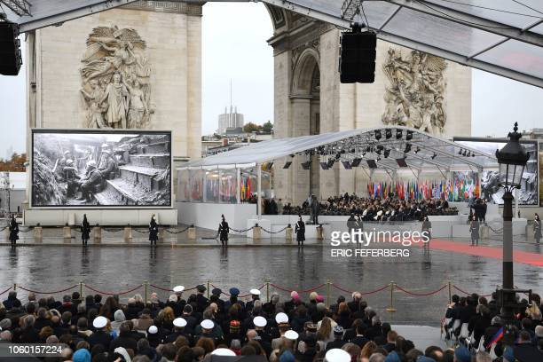 Photos of WWI soldiers are displayed on a giant screen as world leaders attend in a ceremony at the Arc de Triomphe in Paris on November 11, 2018 as...