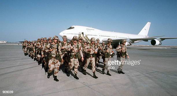 Troops march in formation after disembarking from a Civil Reserve Air Fleet Boeing 747 aircraft upon their arrival in support of Operation Desert...