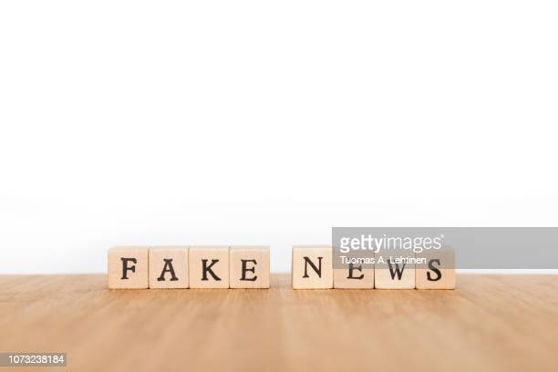phrase made of wooden dice - fake news fotografías e imágenes de stock