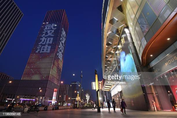 A phrase meaning Cheer up Wuhan is lit on a building in Beijing on Feb 8 amid the spread of the new coronavirus believed to have originated in the...