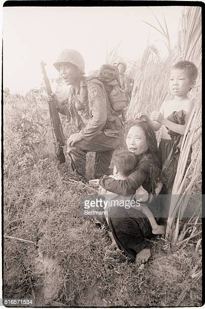 3/23/1966 Phu Cat South Vietnam A Vietnamese mother and her children cringe in terror as Korean troops sweep through a cane field here March 23 in...