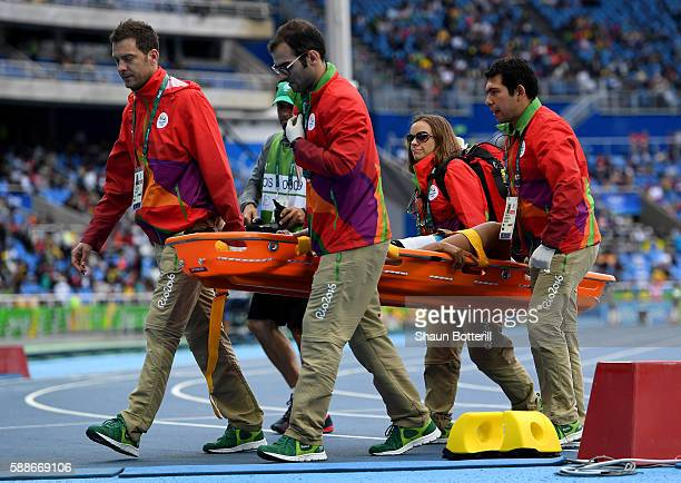 Phumlile Ndzinisa of Swaziland recieves medical attention after being injured in the Women's 100 metres Preliminary Round on Day 7 of the Rio 2016...
