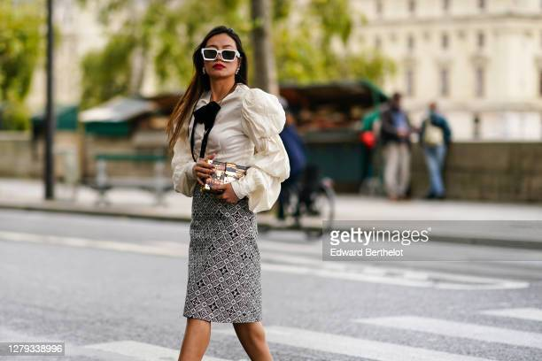Phuong Thythu wears sunglasses, a white ruffled shirt with puff sleeves, a bow tie / lavaliere, a belt, a Petite Malle Vuitton bag, a black and white...