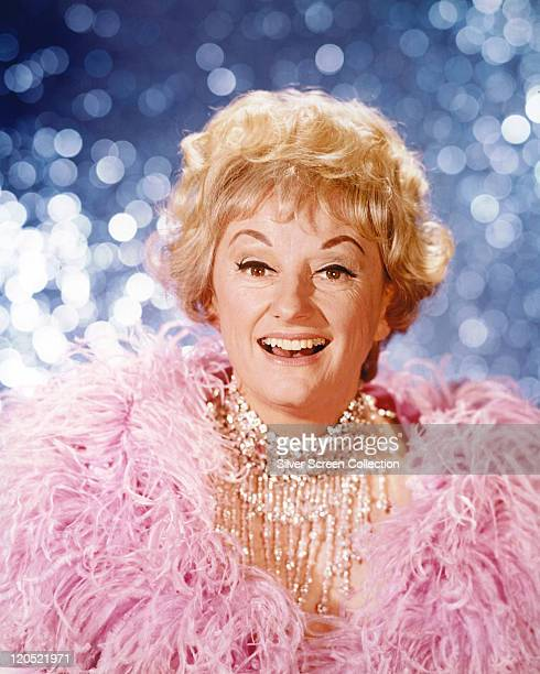 Phyllis Diller US actress and comedian wearing a pink feather boa against a shimmering blue background circa 1965