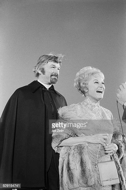 Phyllis Diller with Wade Donovan talking to a reporter Dressed for a formal event circa 1970 New York