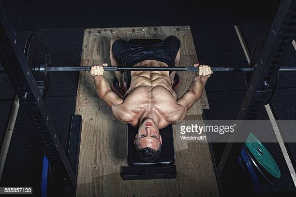 Physical athlete doing barbell bench presses
