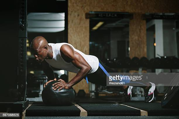 physical athlete doing push-ups on medicine ball in gym - medicine ball stock pictures, royalty-free photos & images
