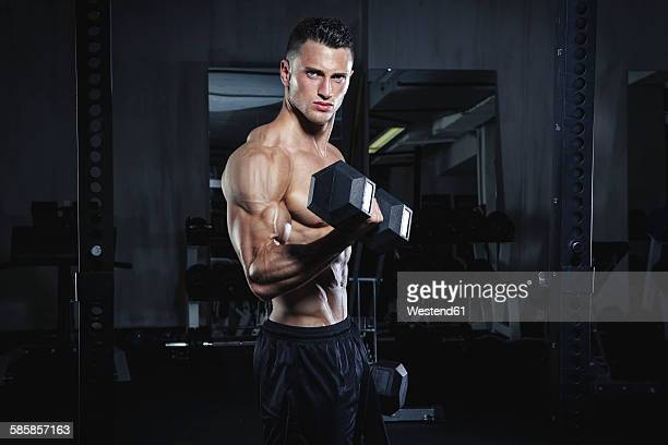 Physical athlete exercising with dumbbells