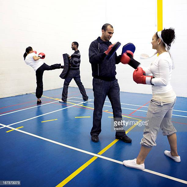 physical education: boxing training lesson with trainers working their athletes - pe teacher stock photos and pictures