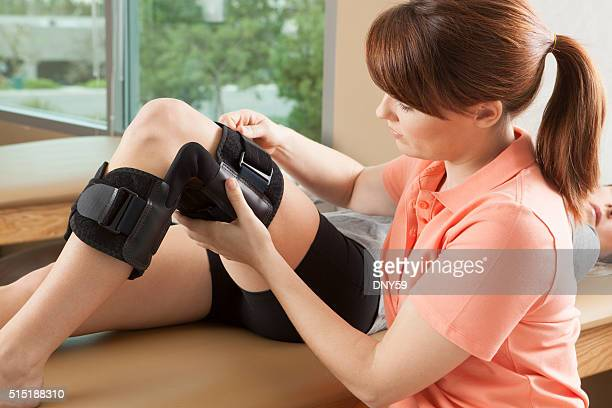 physical therapist adjusting a knee brace on female patient - brace stock pictures, royalty-free photos & images