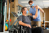Physical Therapist And Patient In Wheelchair Wearing Protective Masks While Therapist Evaluates Range Of Motion