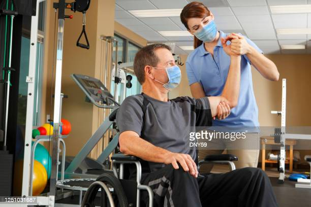 physical therapist and patient in wheelchair wearing protective masks while therapist evaluates range of motion - fisioterapia foto e immagini stock