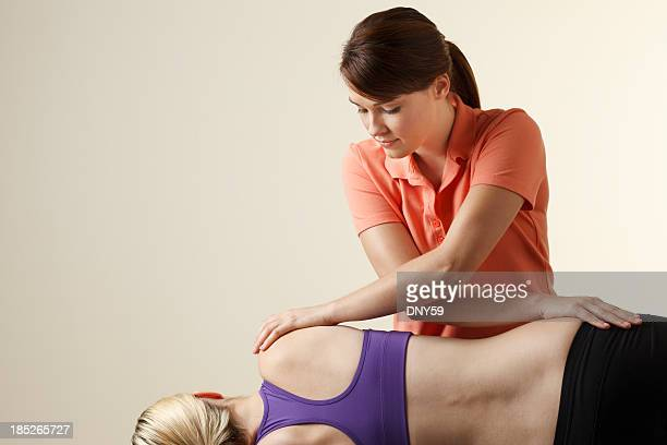 Physical therapist applying massage as treatment to a female patient