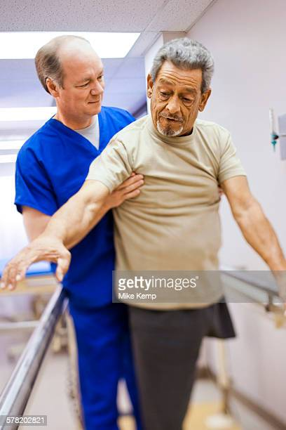 Physical Therapist assisting an older man with one leg in walking