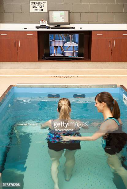 Physical Therapist Assisting Patient with Hydrotherapy in a Underwater Treadmill