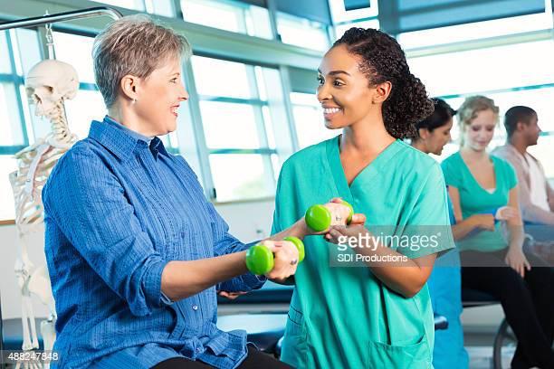 fisioterapeuta ajudando paciente sênior, usando pesos para musculação - physical education - fotografias e filmes do acervo