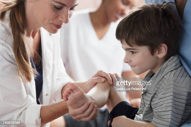 Physical therapist bending leg of boy