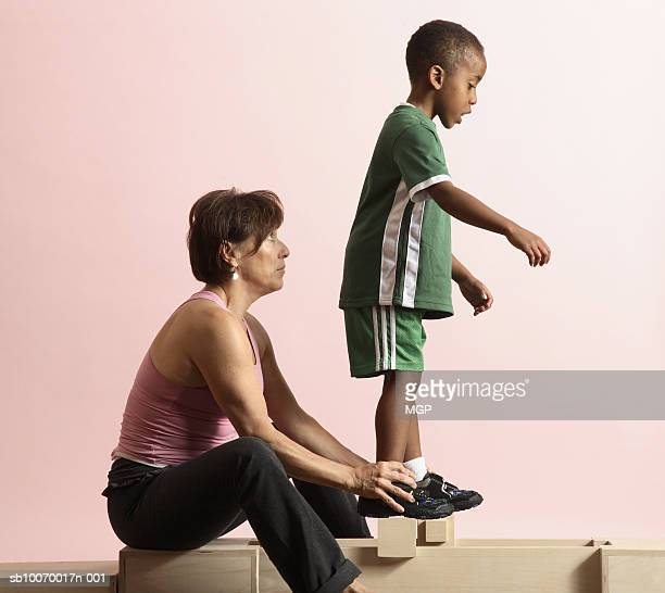 physical therapist doing exercises with boy (4-5), studio shot, side view - 45 49 anni foto e immagini stock