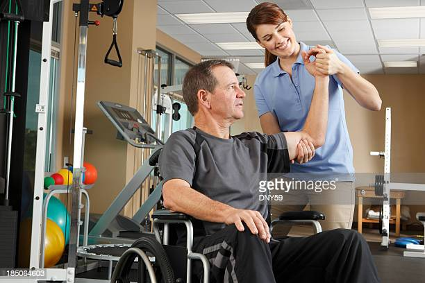 physical therapist evaluating range of motion of patient in wheelchair - paraplegic stock photos and pictures