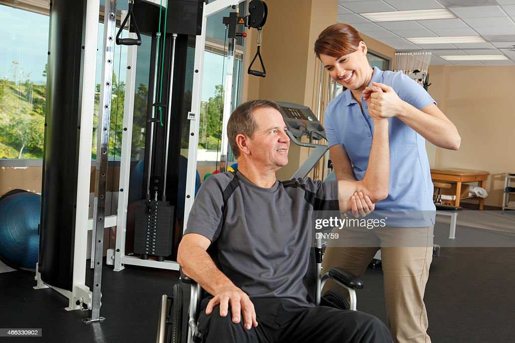 Physical therapist evaluating range of motion of patient in wheelchair : Stock Photo