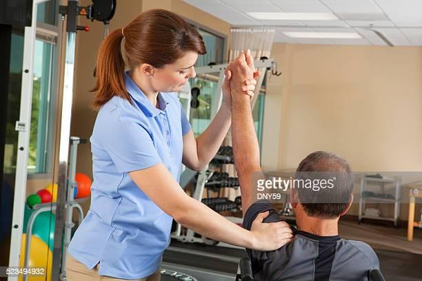 Fisioterapeuta evaluación de la amplitud de movimiento de pacientes para silla de ruedas