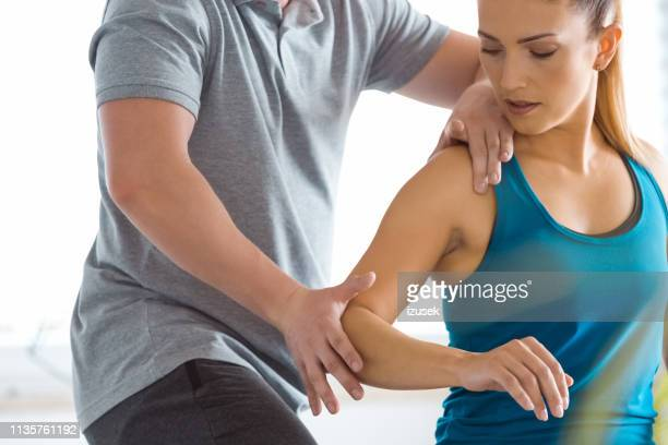 physical therapist examining young woman in rehabilitation center - sports medicine stock pictures, royalty-free photos & images