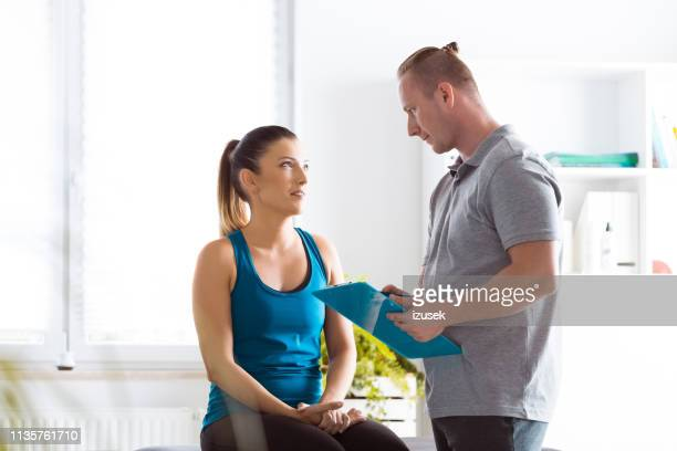 physical therapist examining young woman in rehabilitation center - center athlete stock pictures, royalty-free photos & images
