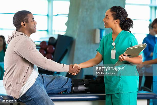 Physical therapist greeting patient in hospital rehab gym