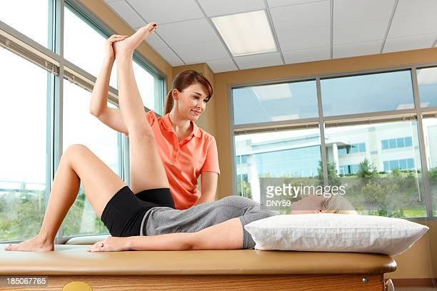 Fisioterapeuta ayudando a una mujer estiramiento su pierna