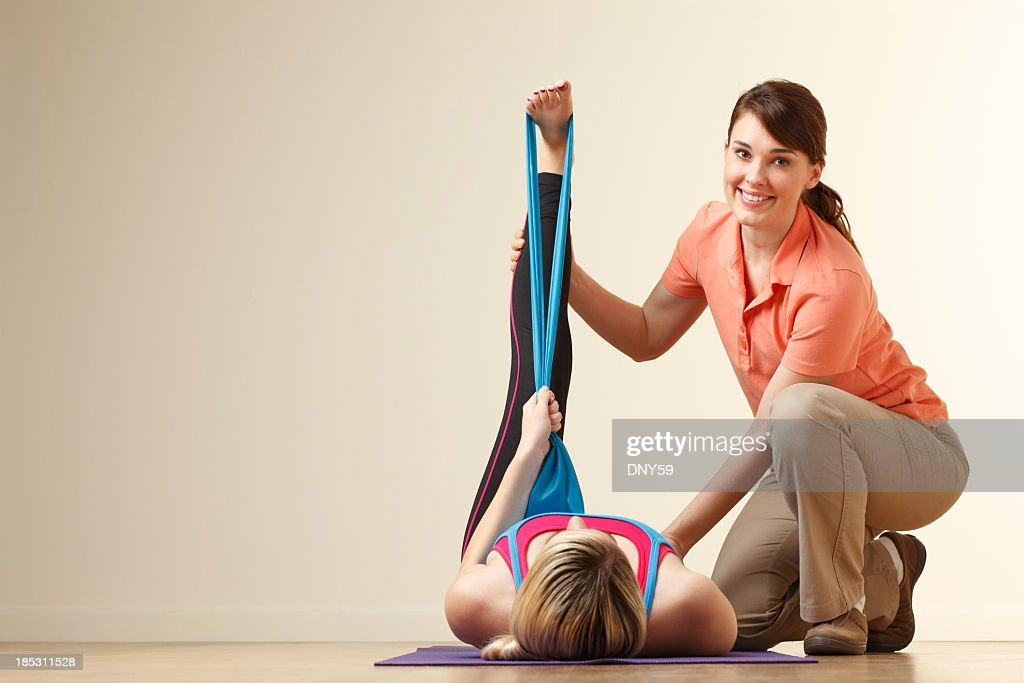Fisioterapista aiutare una giovane donna stretch il tendine del ginocchio : Foto stock
