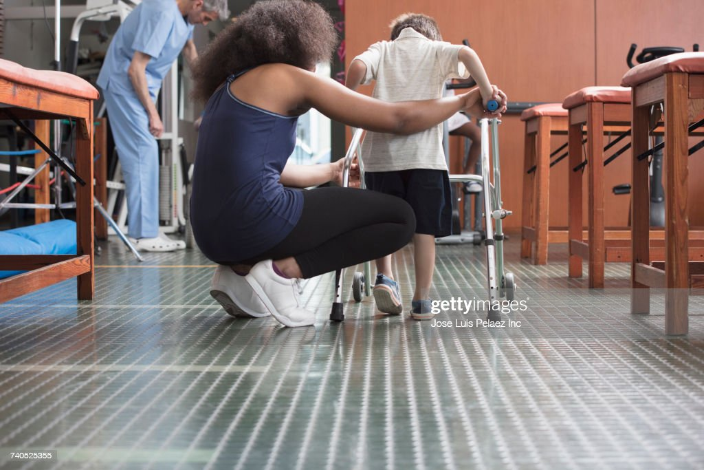 Physical therapist helping boy with walker : Foto de stock
