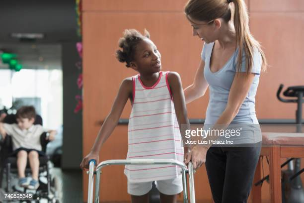 Physical therapist helping girl with walker