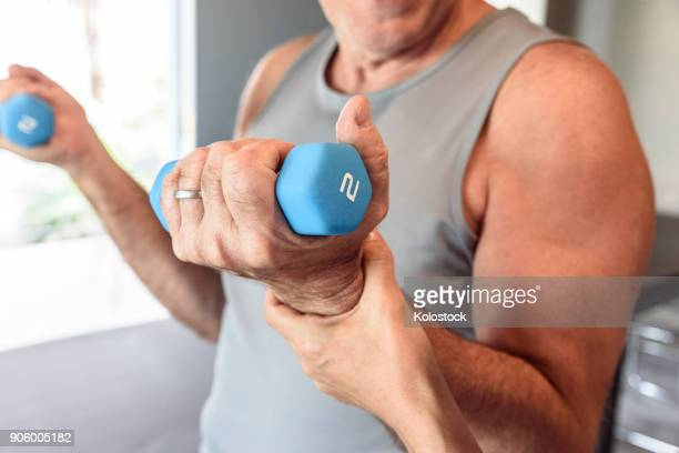 physical therapist helping man lifting weights - mid section stock pictures, royalty-free photos & images